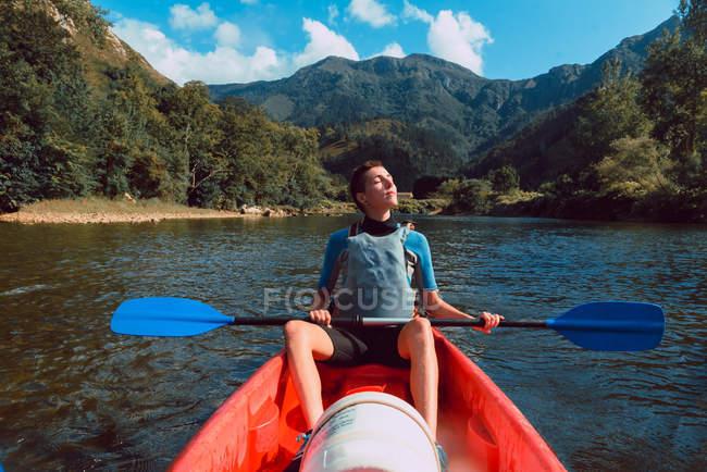 Sportive жінка, що сидить з закритими очима в червоному каное і веслування на Селла спад в Іспанії — стокове фото
