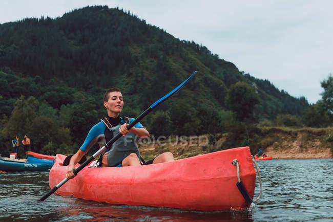Sportive молода жінка з коротким волоссям сидячи в червоному каное і веслування на річці Селла спад в Іспанії — стокове фото
