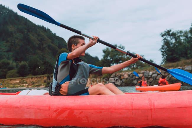 Jeune femme sportive aux cheveux courts assise en canot rouge et pagayant sur le déclin de la rivière Sella en Espagne — Photo de stock