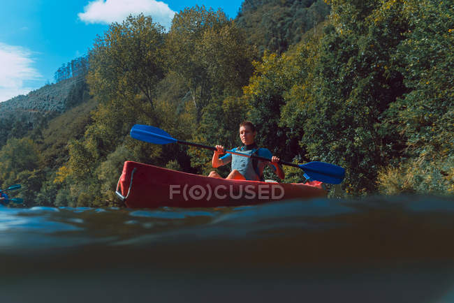 Sportive female canoeist sitting in red canoe and paddling on Sella river decline in Spain — Stock Photo