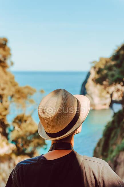 Vista posteriore della donna in cappello in piedi da ringhiera in legno e godendo vista mozzafiato sul mare e scogliere in Ribadedeva Asturie Spagna — Foto stock