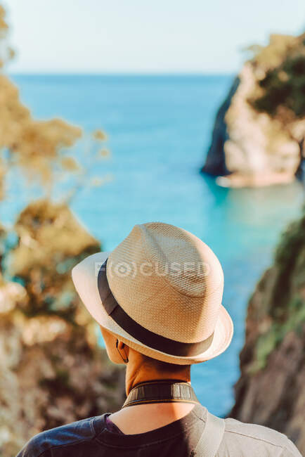 Back view of woman in hat standing by wooden railing and enjoying breathtaking view of sea and cliffs in Ribadedeva Asturias Spain — Stock Photo