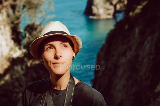 Mujer joven en sombrero de pie con cámara colgando del cuello y disfrutando de pintorescas vistas al mar y las rocas en Ribadedeva Asturias España - foto de stock