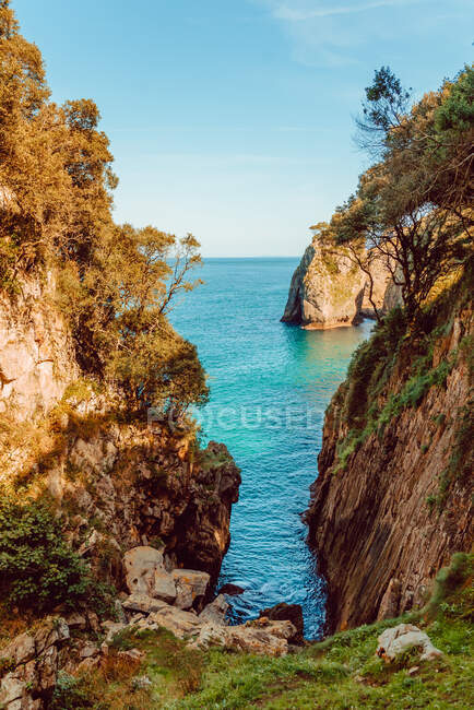 Idyllic landscape with cleft in rocks covered with trees and sea on sunny summer day in Ribadedeva Asturias Spain — Stock Photo