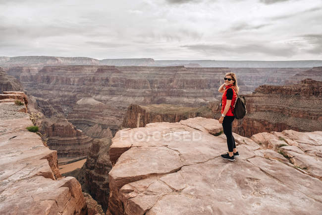 Female hiker with backpack admiring picturesque view of canyon in USA — Stock Photo