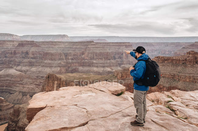 Back view of man with backpack pointing at picturesque view of canyon in USA — Stock Photo