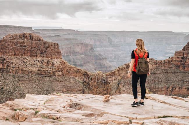 Visão traseira da mulher com mochila admirando a vista pitoresca do cânion nos EUA — Fotografia de Stock