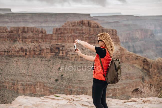 Vista laterale della donna con lo zaino scattare foto di vista pittoresca del canyon negli Stati Uniti — Foto stock