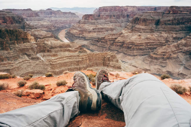 Cropped view of legs of man recreating on edge of cliffs at scenic canyon in USA — Stock Photo