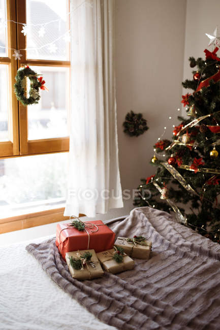 Bett mit Geschenken in Rot und Bastelpapier gegen Weihnachtsbaum. — Stockfoto