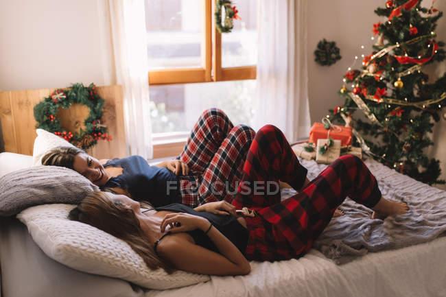 Zwei schöne Mädchen lächelnd im Bett in der Nähe von Weihnachtsbaum in gemütlichen Home Interieur. — Stockfoto