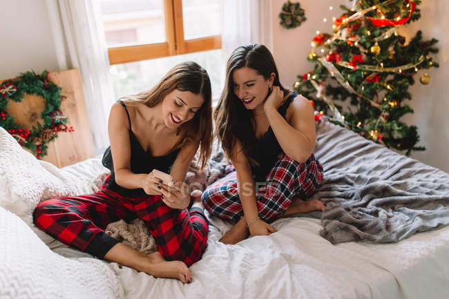 Two female friends at home using mobile phone and taking selfie near Christmas tree in cozy interior. — Stock Photo