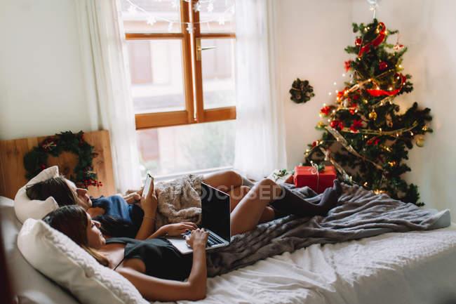 Два друга с помощью ноутбука и смартфона в постели возле елки в уютном интерьере . — стоковое фото