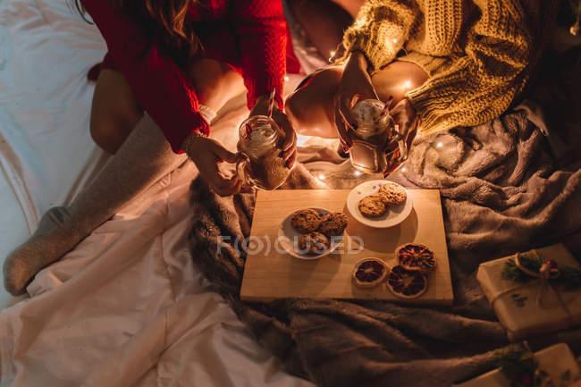 Deux amis en chandail et chaussettes au genou buvant du chocolat chaud et mangeant des biscuits à Noël au foyer. — Photo de stock