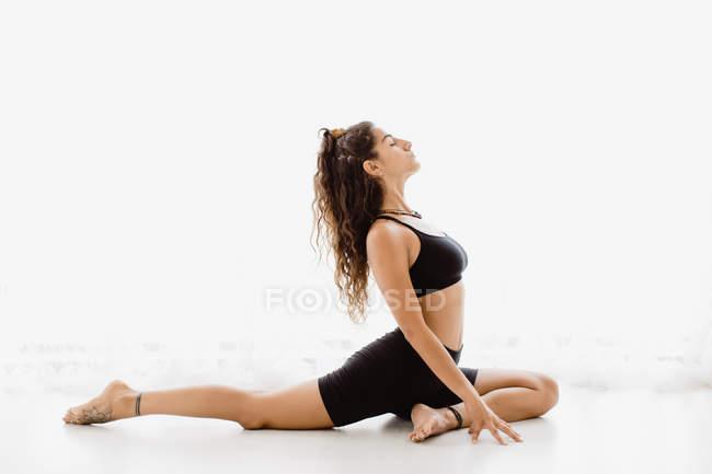 Спортивная женщина, исполняющая голубь йога поза в студии — стоковое фото