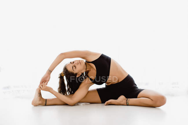 Fit woman performing stretching yoga pose in studio — Stock Photo