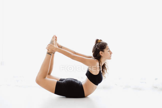 Sportive woman performing stretching yoga pose in studio — Stock Photo