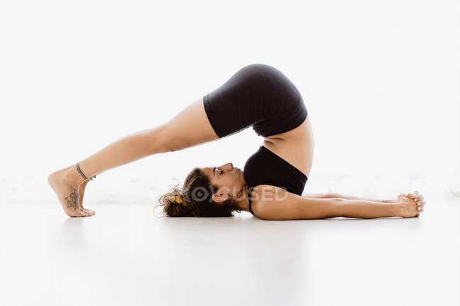 Fit woman performing shoulderstand yoga pose over white background — Stock Photo