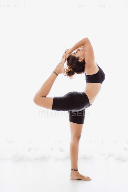 Sportive woman performing stretching yoga pose over white background — Stock Photo