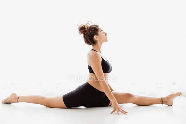 Подходящая женщина, исполняющая позу йоги на белом фоне — стоковое фото
