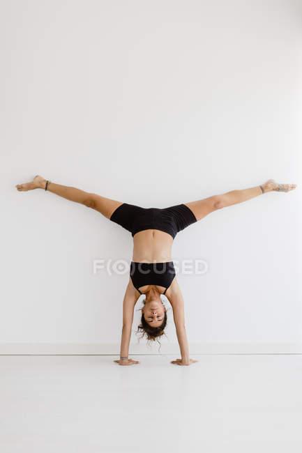 Спортивная женщина, занимающаяся йогой на руках в студии — стоковое фото