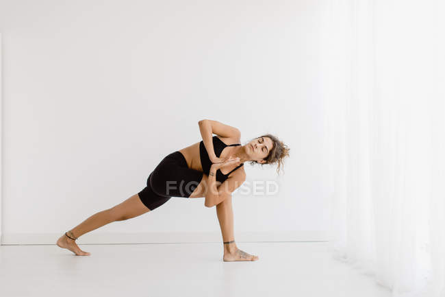 Fit woman performing twist yoga pose over white background — Stock Photo