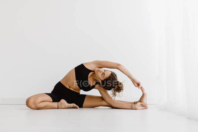Fit woman performing stretching yoga pose over white background — Stock Photo