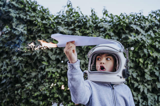 Excited boy in astronaut helmet playing with paper plane with petard in garden — Stock Photo