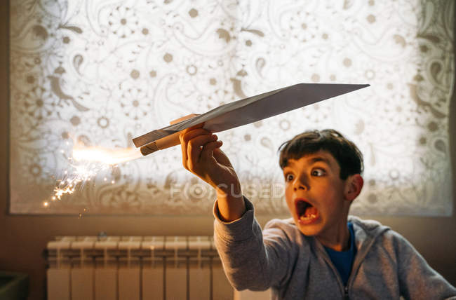 Amused boy playing with paper airplane with petard in room — Stockfoto