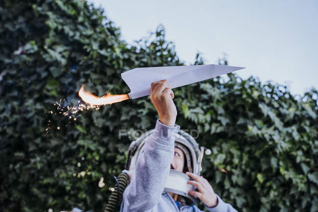 Excited boy in astronaut helmet playing with paper plane with petard in garden — Stockfoto