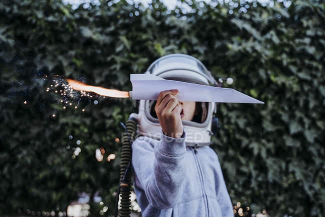 Garçon excité dans un casque d'astronaute jouant avec un avion en papier avec pétard dans le jardin — Photo de stock