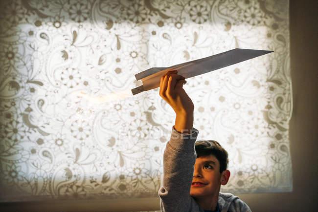Хлопчик, який грає з паперовим літаком з перцем у кімнаті. — стокове фото