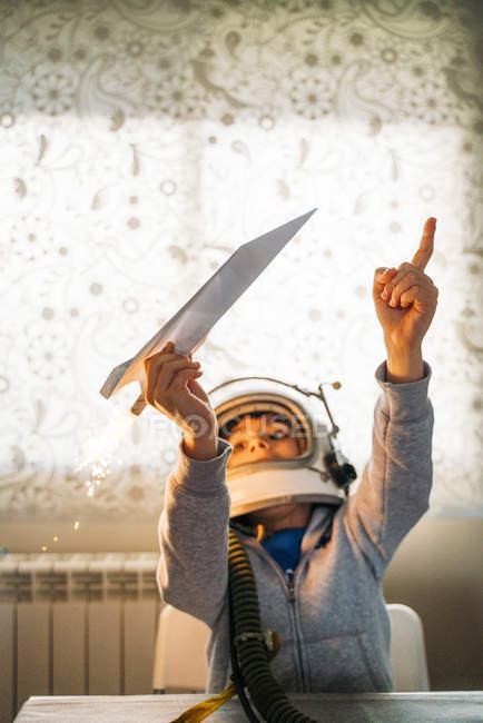 Fantasizing boy in astronaut helmet playing with paper plane at home — Stockfoto