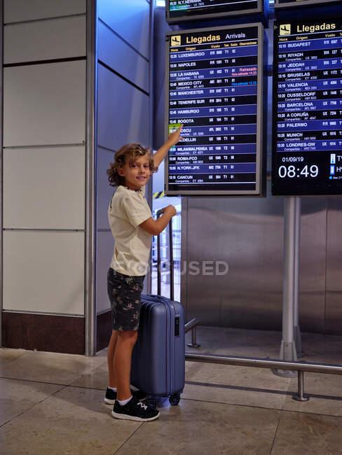 Garçon avec valise à côté d'un tableau de bord à l'aéroport au Portugal — Photo de stock