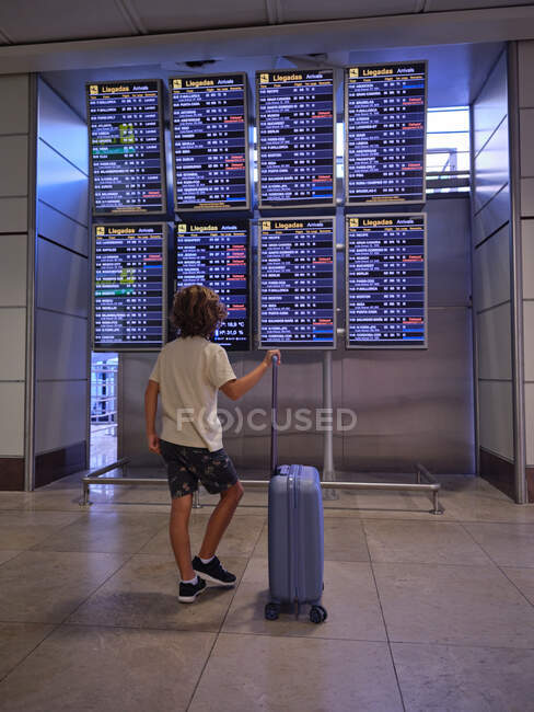 Back view of boy with suitcase looking at scoreboard in airport in Portugal — Stock Photo