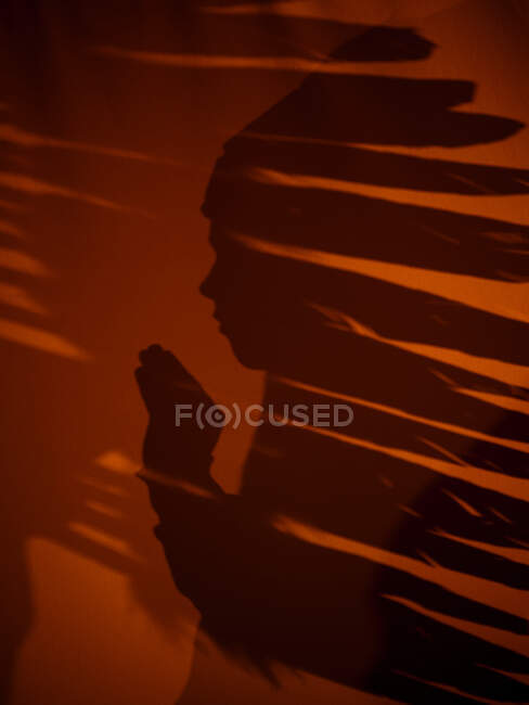 Side view of shadow of boy in ceremonial Indian feather hat on orange background in Portugal — Stock Photo