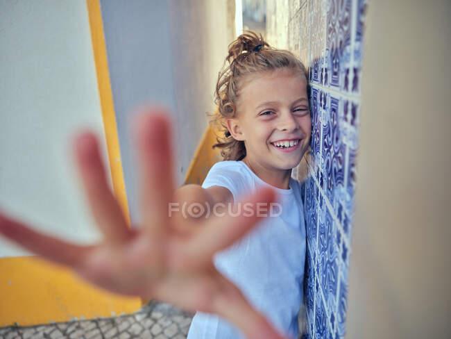 Селективный фокус контента ребенка, опирающегося на стену в Португалии и смотрящего в камеру — стоковое фото