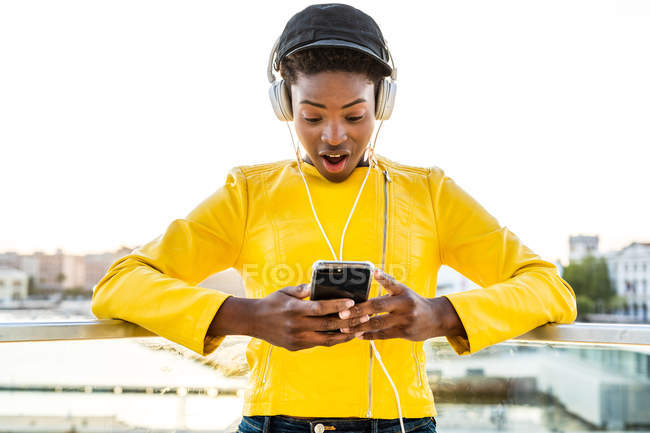 Афроамериканка в стильной яркой куртке с помощью мобильного телефона и прослушивания музыки на наушниках — стоковое фото