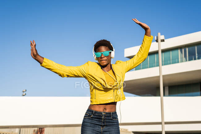 Low angle of happy African American woman jumping with hands up on street — Stock Photo