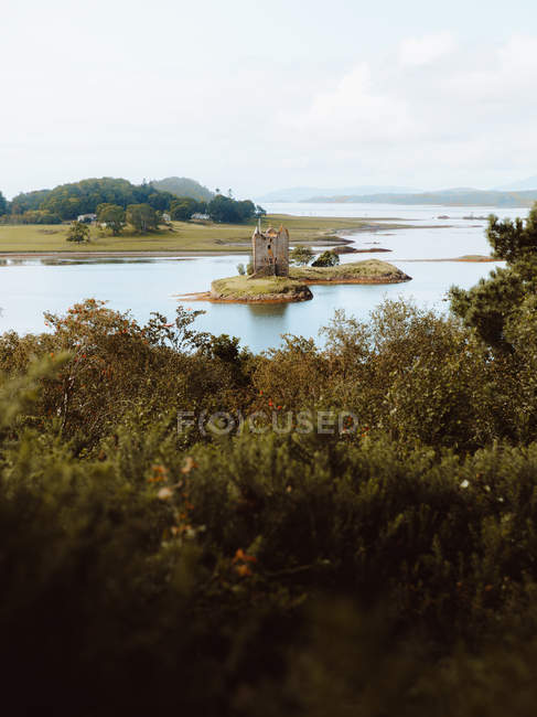 Damaged old castle located on coast of calm lake against grassy hills on cloudy day in UK countryside — Stock Photo