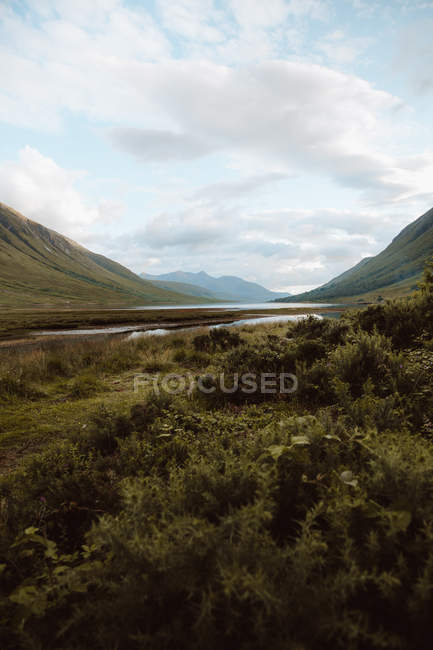 Idyllic landscape of high green mountains and valley with tranquil river under cloudy sky in Glen on summertime — Stock Photo