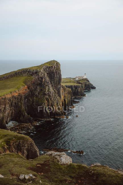 Dall'alto maestosa vista del Faro di Neist Point costruito su alte rocce circondate da acqua scura di giorno — Foto stock