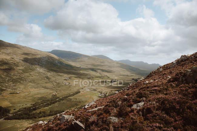Vue à couper le souffle de rochers et de collines couverts d'herbe verte et brune et de pierres sous un ciel couvert le jour — Photo de stock