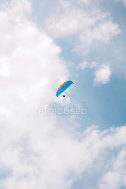 Dal basso persone che volano con parapendio colorato nel cielo nuvoloso vicino a Durdle Door durante il giorno — Foto stock