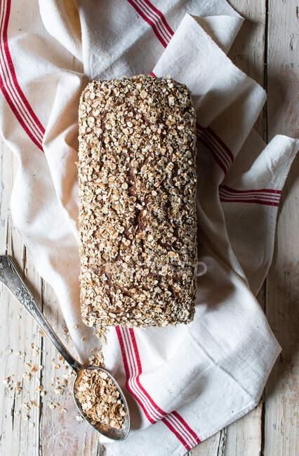 Сверху буханка вкусного хлеба из райкорна, помещенного на салфетке рядом с ложкой зерна на деревянном фоне — стоковое фото