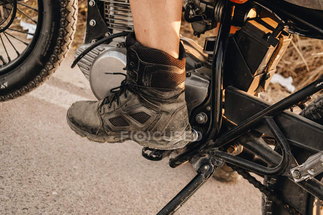 Foot in boot of male riding moto on asphalt road — Stock Photo