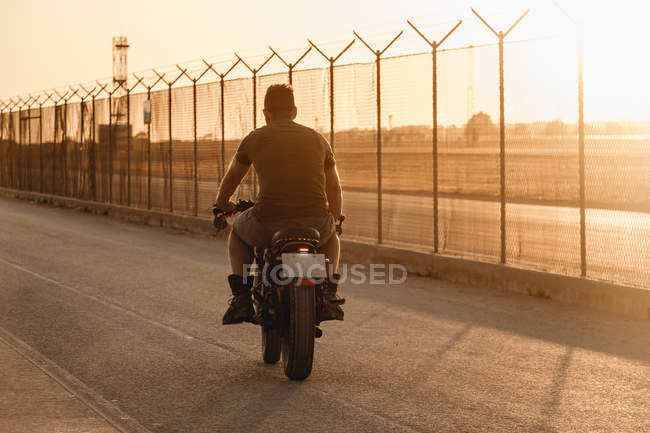 Сильный человек за рулем мотоцикла на закате, вид сзади — стоковое фото