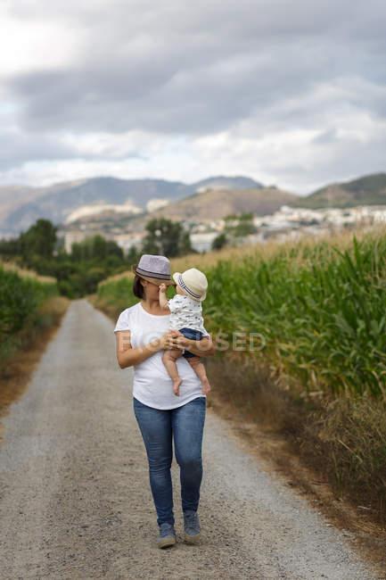 Adorável mãe e filho na mão desfrutando e rindo no campo — Fotografia de Stock