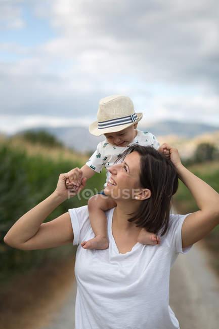 Criança adorável em chapéu olhando para a mãe — Fotografia de Stock