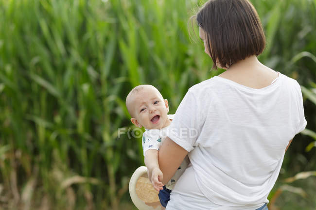 Adorable mother and child on hand enjoying and laughing in field - foto de stock